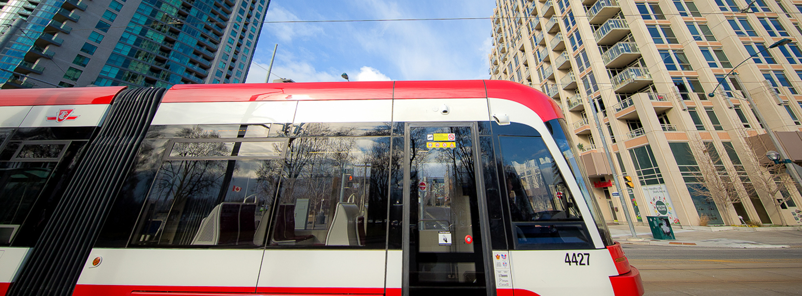 streetcar travelling pass two buildings